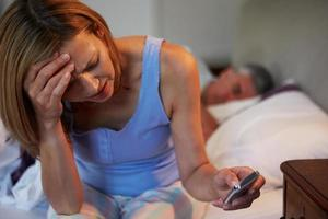 A woman suffering from insomnia while her husband sleeps photo