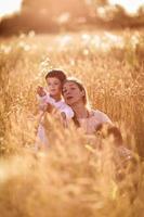 madre abrazando a su hijo e hija en un campo de trigo