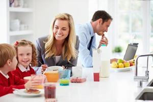 família tomando café da manhã na cozinha antes da escola e do trabalho