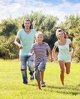 pareja con niño jugando corriendo en verano foto