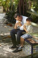rapaz comendo sanduíche com seu pai