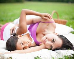Mother and daughter lying on picnic blanket