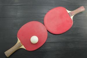 Two red table tennis rackets on dark background