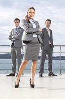 confiant, femme affaires, debout, collègues, terrasse, contre, ciel