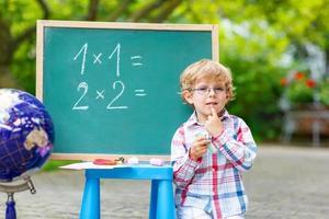 Lindo niño pequeño con gafas en la pizarra practicando mathem