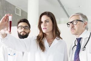 jóvenes doctores examinan tubo de sangre en laboratorio foto