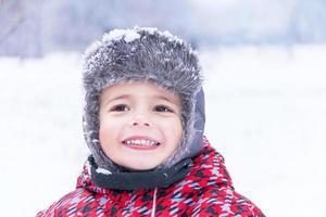 Portrait of a little cute boy on winter background.
