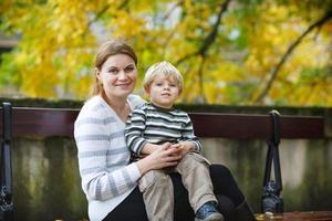 Adorable pequeño hijo y madre en la ciudad de otoño. foto