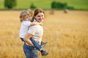 Young mother and little son having fun on hay field