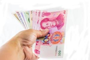 monnaie yuan chinois en main sur fond blanc