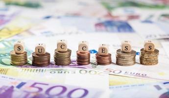 éxito de la palabra en pilas de monedas, fondo de efectivo