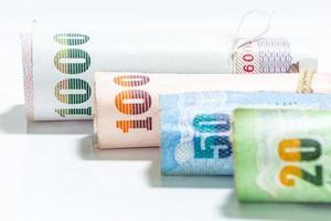 Billetes de dinero tailandés sobre fondo blanco.
