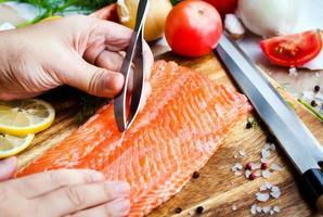 Process of cutting raw salmon photo