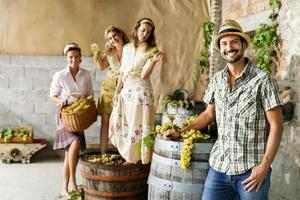 farmer drinks wine while women pounding grapes