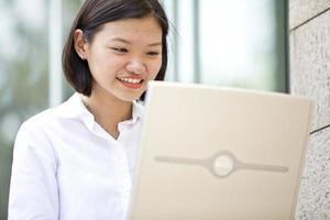 jovem executivo feminino asiático usando laptop pc na área de negócios