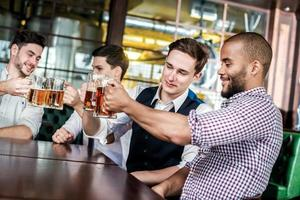 Four businessmen friends drink beer and spend time together