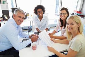 cuatro colegas reunidos alrededor de una mesa en una oficina