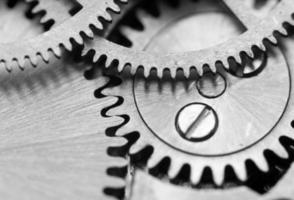 Fondo blanco negro con ruedas dentadas de metal un mecanismo de relojería. macro foto