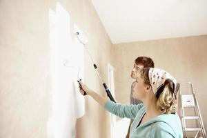 pareja pintando la pared con rodillos de pintura foto