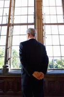 empresário com braços atrás das costas, olhando pela janela, vista traseira