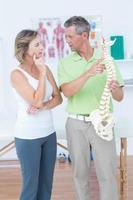 médico mostrando columna anatómica