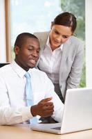 Businessman And Businesswoman Using Laptop In Office