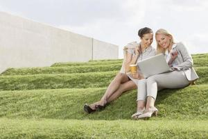 Happy businesswomen looking at laptop while sitting on grass steps