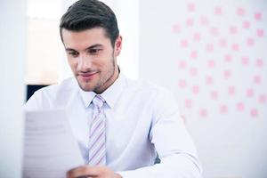 Businessman reading document in office photo