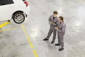 Mechanics talking in garage photo