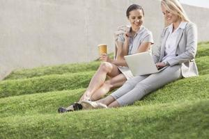 Happy businesswomen looking at laptop while sitting on grass