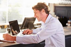gerente de restaurante masculino trabajando en la computadora portátil foto