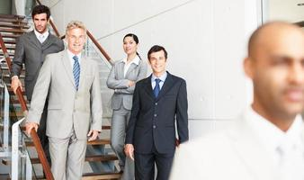 Close-up of businessman with colleagues standing in background photo