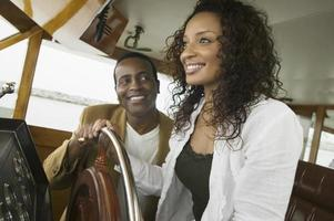 Couple At Steering Wheel Of Yacht