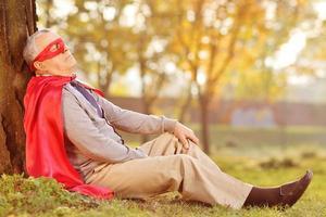 Senior en traje de superhéroe apoyándose en el árbol