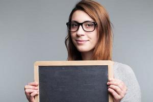 mujer mostrando pizarra en blanco foto