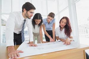 equipo de negocios leyendo planes de trabajo foto