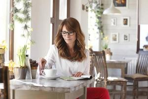 Beautiful woman sitting at desk in coffee shop photo
