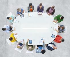 las personas con ropa brillante se sentaron alrededor de la mesa de conferencia ovalada