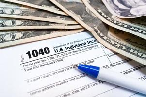 1040 Individual tax return form close-up with pen and dollars