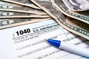 Primer plano del formulario de declaración de impuestos individual 1040 con bolígrafo y dólares foto