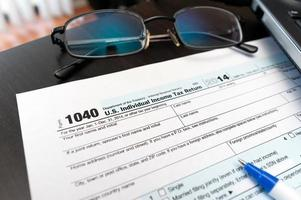 1040 Individual tax return form close-up next to eye glasses