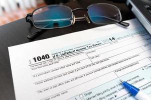 Formulário de declaração de imposto individual 1040 close-up ao lado de óculos