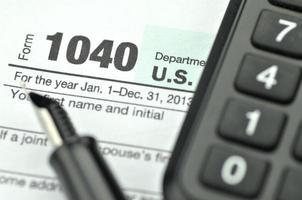 primer plano de nosotros formulario de impuestos, bolígrafo y calculadora foto