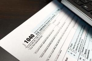 Primer plano del formulario de declaración de impuestos 1040 con computadora portátil foto