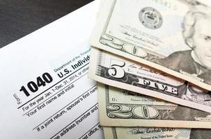 Formulario de declaración de impuestos individual 1040 de cerca y billetes de dólar foto