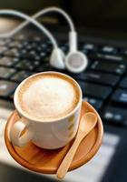 Coffee cup with  headphones on laptop