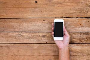 Man hand holding smart phone on wood background