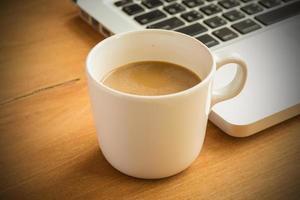 tazza e computer portatile di caffè caldi del latte su fondo e su struttura di legno.