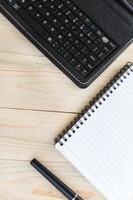 mesa de oficina con cuaderno, bolígrafo y teléfono inteligente foto