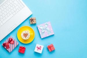 computadora con bxes de regalo y capuchino foto